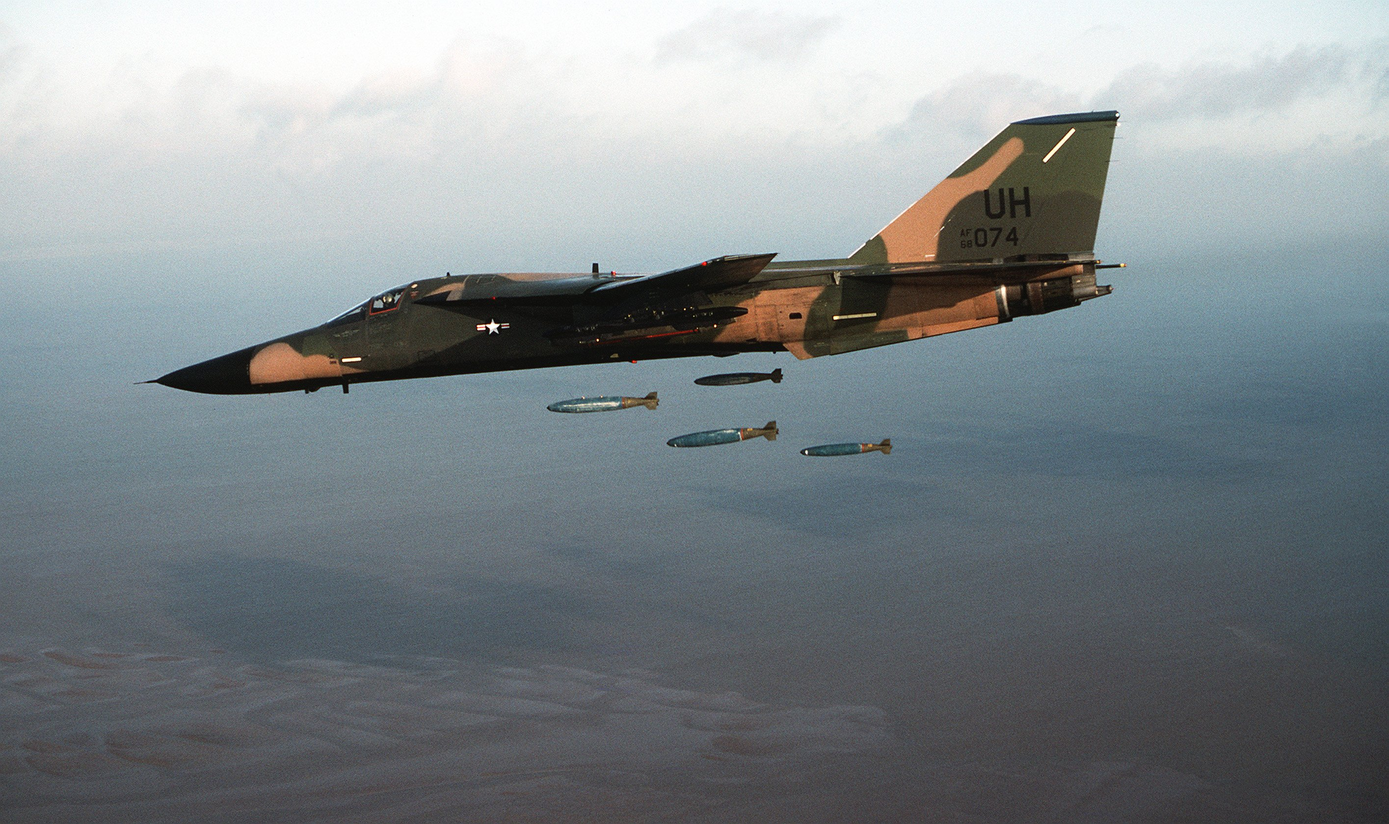left side air to air view of an f 111 aircraft dropping four bombs ...